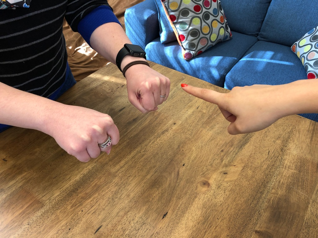 One person presenting closed fists with a second person pointing at one.