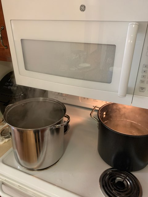 Two pots of maple sap being boiled down to syrup
