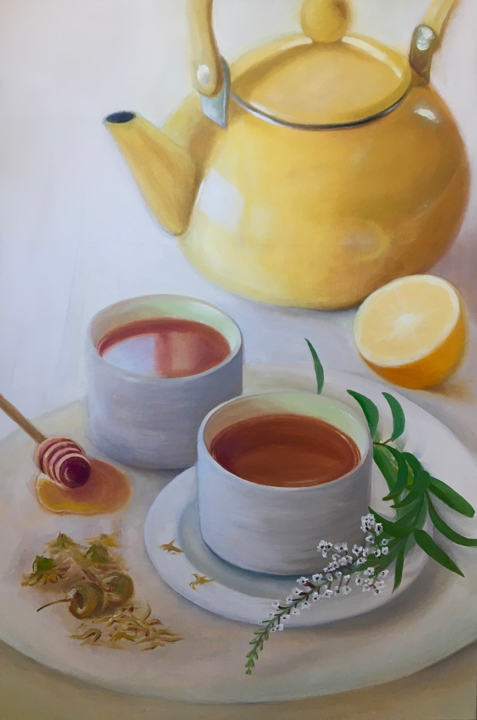Cups of tea on a platter with a teapot and lemon in the background